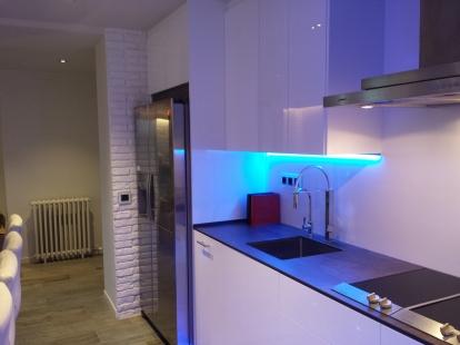 Detalles de la cocina iluminada en led azul y en color blanco sin tiradores.