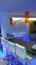 Entramos en la cocina; Vemos con más detalle el blanco de los taburetes y las coloridas lámparas de techo.